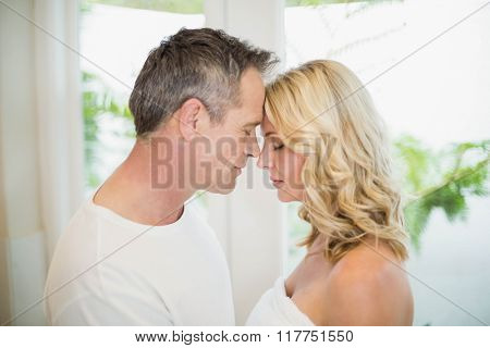 Cute couple hugging about to kiss in the living room