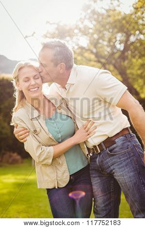 Husband kissing wife on the cheek outside