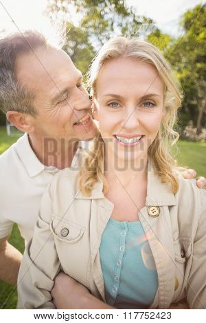Husband whispering something to wife's ears outside