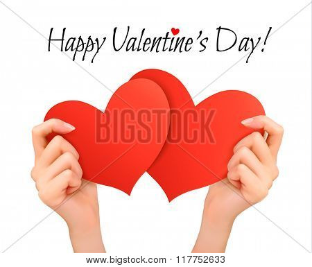 Holiday valentine background with hands holding two red hearts.