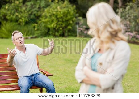 Upset couple having an argument in the garden