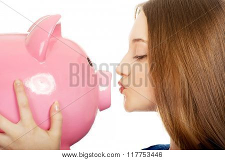 Teenage woman kissing piggybank.