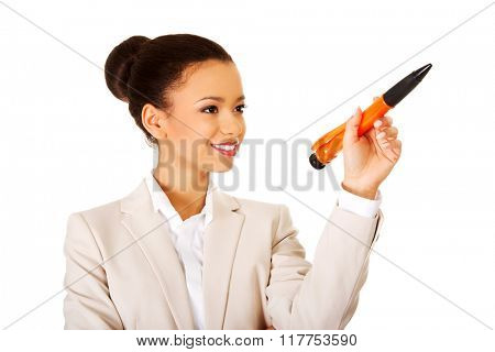 Businesswoman pointing up with big pen.
