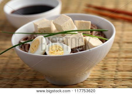 Soba noodle soup with boiled egg, tofu, daikon radish and green onion
