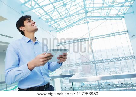 Businessman leaning on balcony railings