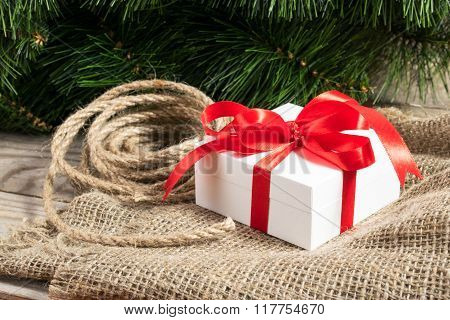 White Gift Box With Red Ribbons, Cristmas Tree Branch And Rope On Sackcloth On Wooden Background
