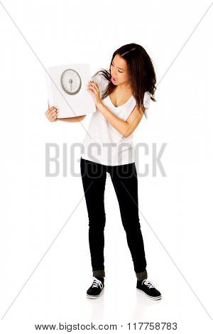 Shocked woman holding a scale.