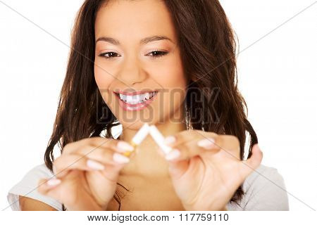 Young woman breaking a cigarette.