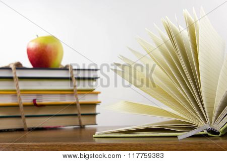 A stack of colorful books, open book.