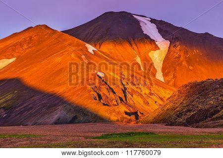 Morning dawn  National Park Landmannalaugar, Iceland. Mountains and glaciers covered with warm pink and orange sunlight