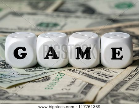Four white dice placed on pile of money spelling GAME word