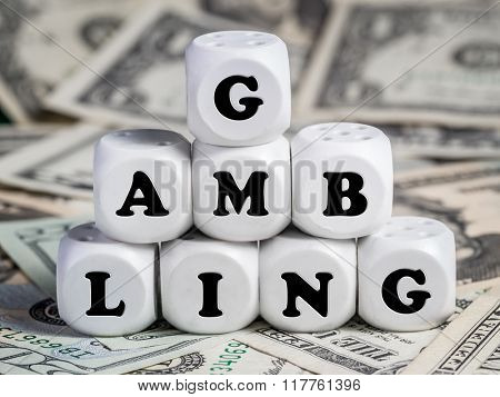 Eight white dice placed on pile of money spelling GAMBLING word