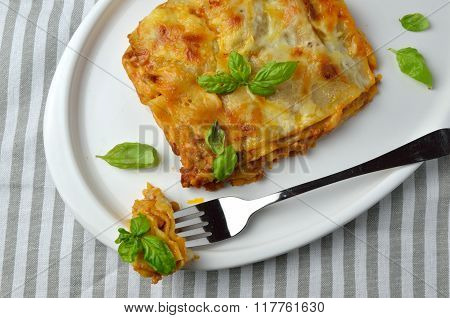 Juicy Lasagne And Leaves Of Basil On Plate