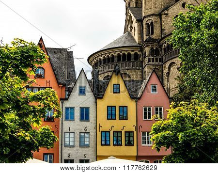 A row of colorful houses on the banks of the Rhine in front of the St. Martin Church in Cologne, Ger