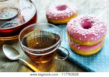 Cup Of Tea With Pink Glazed Donuts On Wooden Background