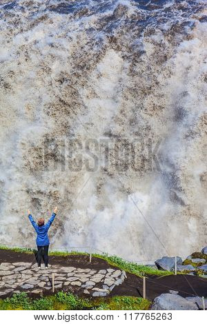 Elderly woman admires the picturesque spectacle. Colossal roaring waterfall cascading into the abyss. Dettifoss, Iceland, Jokulsargljufur National Park
