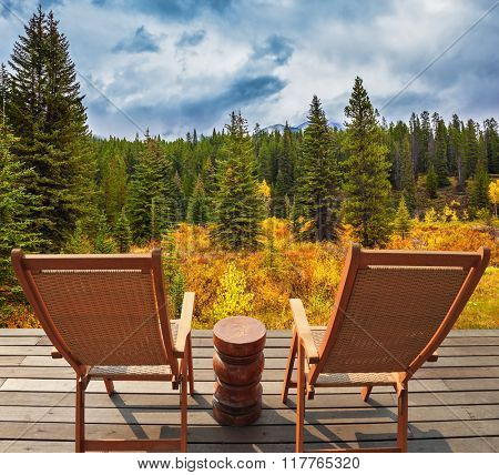 On the wooden platform there are two wicker deck chairs. The lush colorful autumn in the Rocky Mountains of Canada