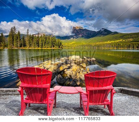 Pyramid Mountain reflected in Pyramid Lake. Two red chaise lounges for the tourists connected among themselves by table
