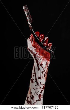 Bloody Halloween Theme: Bloody Hand Holds A Razor Sharp Old With A Dangerous Edge Isolated On Black