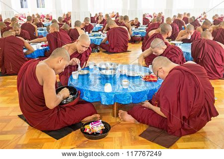 BAGO, MYANMAR -November 26, 2015: Monks having lunch in the monastery at Bago Myanmar. Buddhism in Myanmar is predominantly of the Theravada tradition, practised by 89% of the country's population