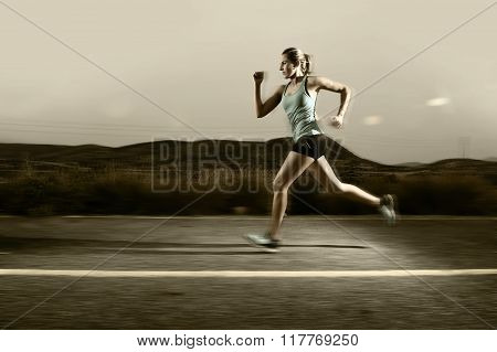 Young Fit Sport Woman Running Outdoors On Asphalt Road In Mountain Landscape On Evening With Harsh L