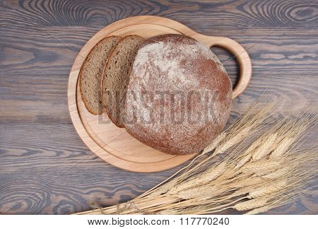 Bread and wheaten ears on wooden background top view