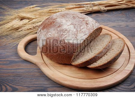 Bread and wheaten ears on wooden background