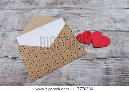 Valentine Day background with brown envelope and hearts on wood