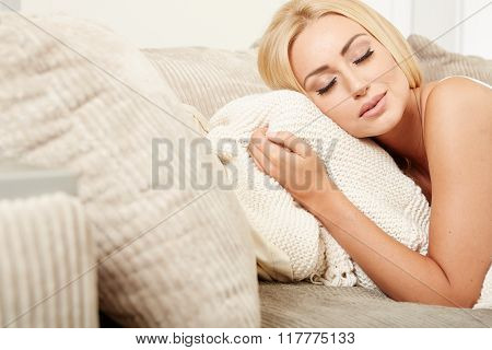 Attractive young woman lying relaxing on a sofa
