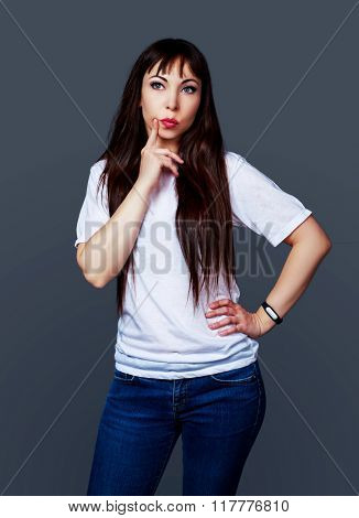 thoughtful young brunette woman against grey studio background