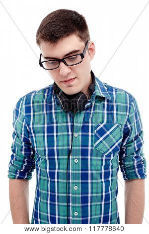 Front portrait of young man wearing black glasses and blue checkered shirt standing with headphones on his neck and looking aside isolated on white background