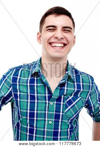 Front portrait of young man wearing blue checkered shirt laughing out loud with closed eyes isolated on white background - laughter concept
