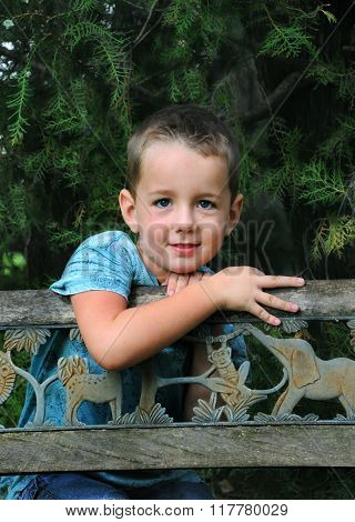 Little boy enjoys his boyish day dreams as he leans against a wooden bench in wooded park. He has on a blue shirt and jeans.