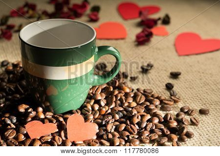 Cup of coffee with beans and hearts scattered paper