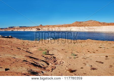Houseboat is docked along the beautiful sandstone rocks and cliffs of the Glen Canyon National Recreation Area in Arizona.