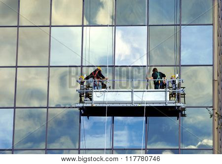 Two men raise the scaffolding that will be their platform to work form. They are cleaning the windows on a high rise office building in Hancock Michigan.