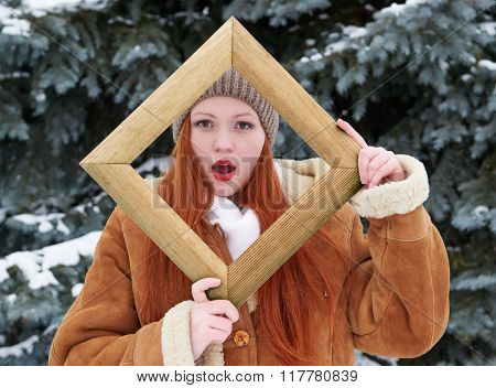 Woman outdoor portrait in wooden photo frame at winter season. Snowy weather in fir tree forest.