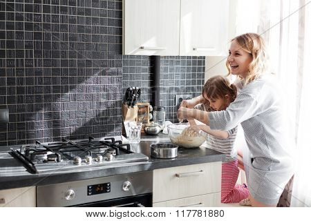Mom with her 5 years old child cooking holiday pie in the kitchen to Mothers day, casual still life photo series