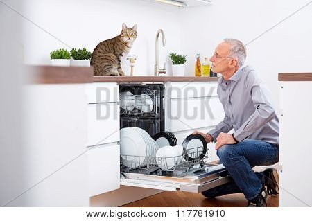 Senior Man With Cat In The Kitchen