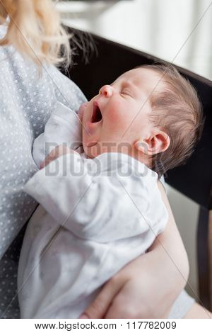 Young mother is holding her sleeping newborn baby