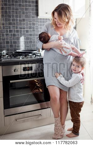 Young mother is holding her newborn baby and toddler at the kitchen