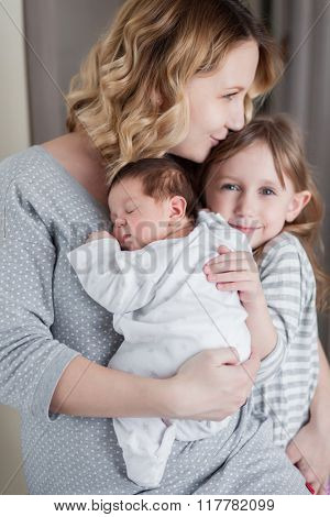 Young mother is holding her newborn baby and hugging her children
