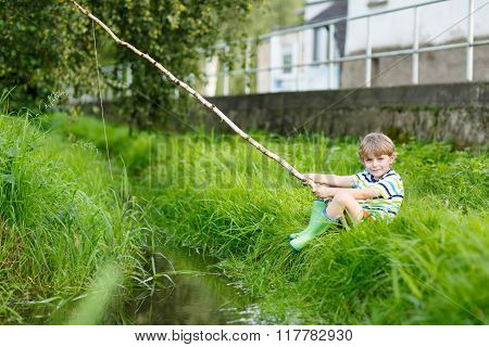 Little kid boy fishing on river with selfmade fishing rod