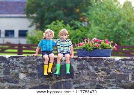 Two little kid boys sitting together on stone bridge