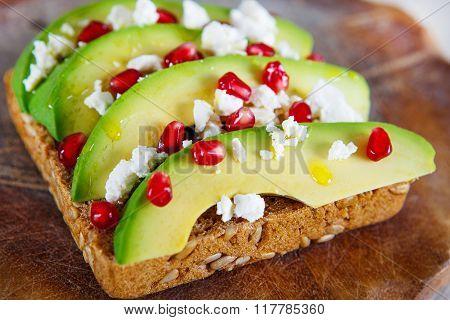 Avocado with Feta, pomegranate on sunflower seeds bread sandwich