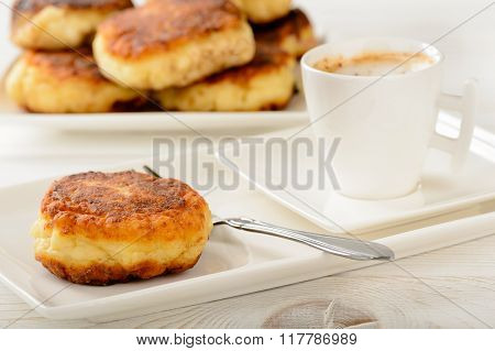 Cheese pancakes on white plate and cup of coffee.