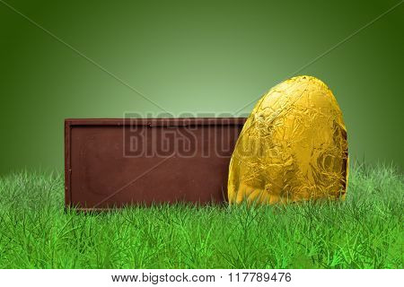 Chocolate bar and golden Easter egg on grass on green background