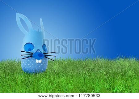 Funny easter blue bunnyon grass on blue background