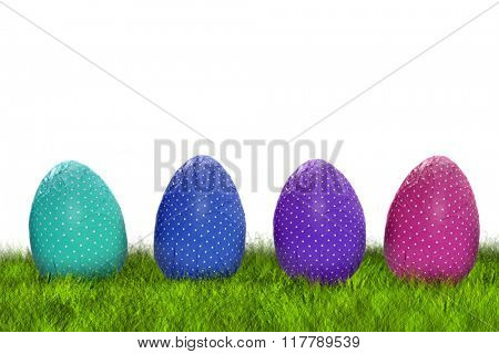 Four wrapped dotted Easter eggs on grass on white background