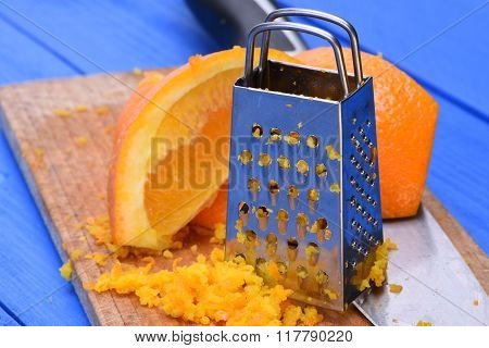 Orange fruit and orange zest with grater on wooden board